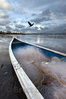 A fishing boat at dusk on Chowpatty Beach, Mumbai, India.