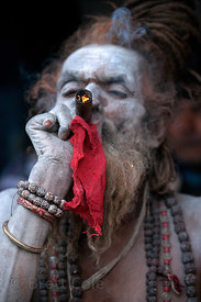 A Naga Sadhu (holy man) smokes a pipe and meditates at a staging area in Kolkata, India for pilgrims going to the Gangasagar ...