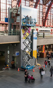 Replacing a poster on the lift hoistway at Antwerp Central Station
