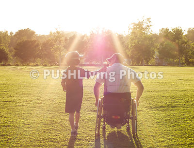 Father in a wheelchair playing baseball with his son