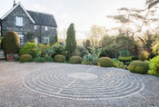 Pavement maze created with stone setts in gravel in the driveway, surrounded by clipped yew spheres and other shrubs. York Ga...