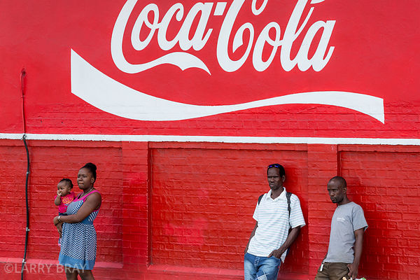 people leaning against red coca cola wall in Castries, St Lucia