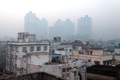 Air pollution over the tallest buildings in Kolkata, India - the 35-story apartments near South City Mall.