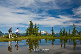 Two day hikers doing the Perry Creek–Mt. Forgotten Measdows Trail, with Glacier Peak viewed from a tarn in Mt. Forgotten Mead...