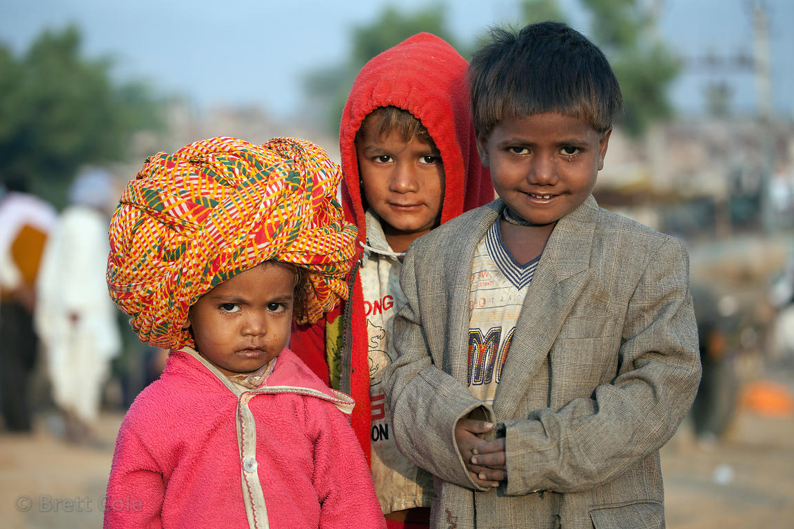 A boy wears an adult-sized turban at the Pushkar Camel Mela, Pushkar, India.