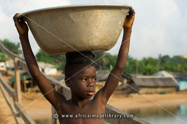 Girl carrying water near Busua, Ghana
