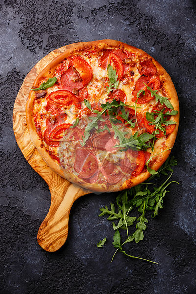 Pizza with ham, tomato and arugula leaves on wood olive cutting board on dark lava background