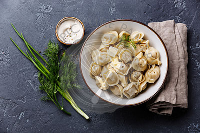 Russian pelmeni meat Dumplings with sauce sour cream and greens in bowl on dark stone background