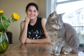 Grey Cat Sitting on a Table In Front of a Young Woman