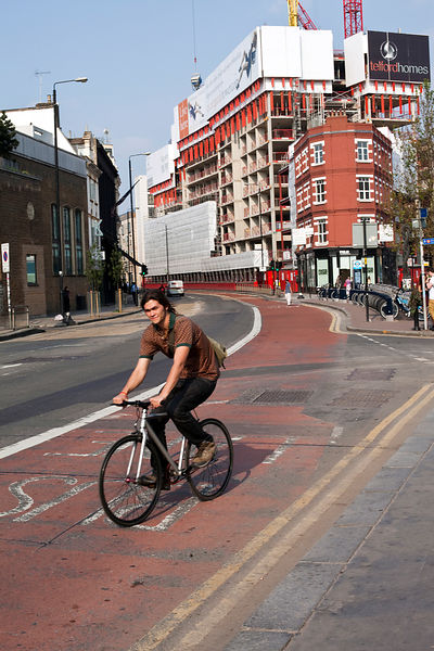 UK - London - A young man rides his bicycle down the Hackney Road near Brick Lane
