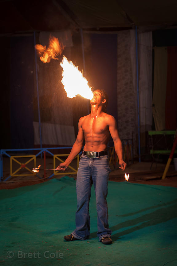 A man breathes fire as part of a circus act in Pushkar, Rajasthan, India.