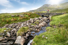 A hiker crossing Torver Bridge near Coniston on a sunny summers day in the English Lake District.