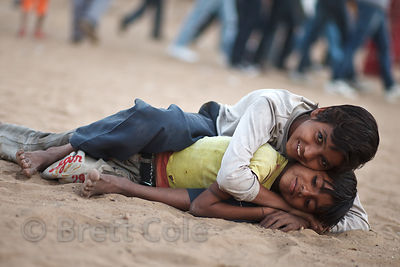 Boys wrestling in the sand, Rajasthan, India