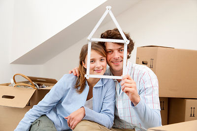 Smiling couple holding house symbol
