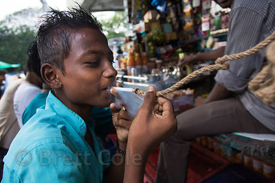 A boy lights a cigarette using the smoldering end of a piece of dense rope, Newmarket, Kolkata, India