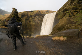 A photographer at the Skogafoss Waterfalls on the Skógá River in the south of Iceland.