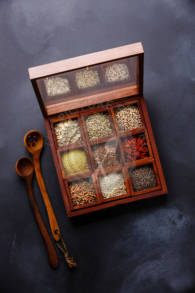 Superfoods and cereals selection in wooden box: oat, buckwheat, quinoa, bulgur, flax seed, goji berry, polba, sesame and chia on dark background