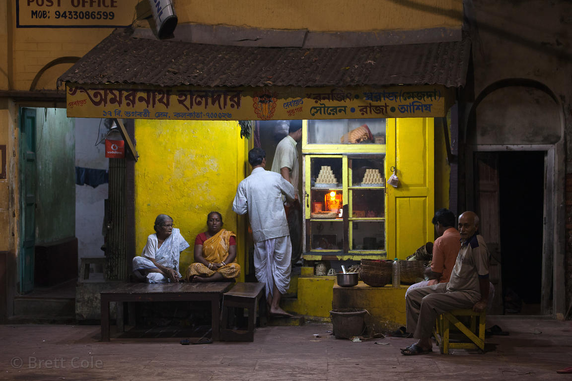 Painterly nighttime scene in a courtyard in Kalighat, Kolkata, India.