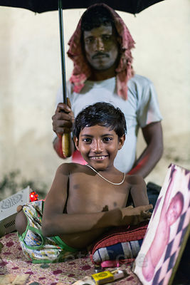 A boy with no legs, accompanied by his father. Next to him is a photo from when he was a baby, Newmarket, Kolkata, India