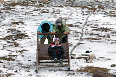 Two men (workers, not his parents) push a boy in a sled at Snow Point on Rohtang Pass, Manali, India