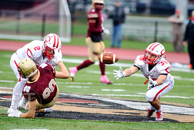 Coe College's Trevor Noble and Central's Tyler Olson (2) and Max Barkalow (28) jockey for a incomplete pass during the second...