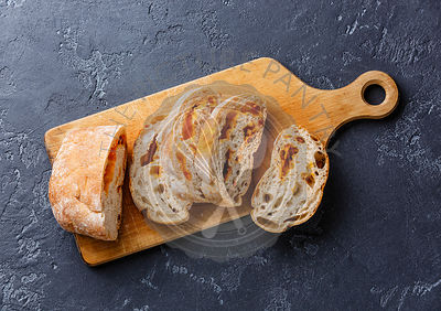 Sliced bread Ciabatta with cheese on cutting board on dark background