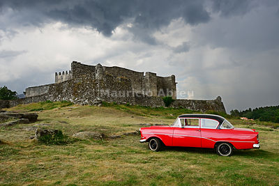 The 13th century old castle of Lindoso, keeping an eye on the Spanish mountains ahead, and a vintage Opel Rekord. Peneda Gere...