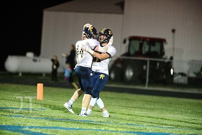 Iowa City Regina's Jacob Phillips (21) celebrates with teammate Isaac Vollstedt (44) after Phillips' touchdown against Wilton...