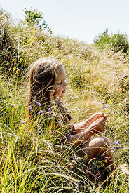 Little girl in the grass picking flowers.jpg