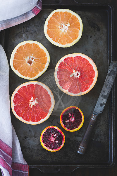 Pink grapefruit and blood oranges on a baking tray.
