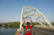 Woman walking over the suspension bridge over the Lower Volta river, Akosombo, Ghana