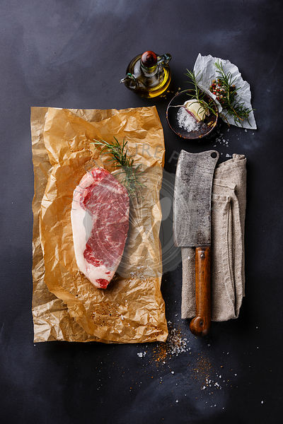Raw fresh meat steak Striploin with salt and pepper and Butcher Meat cleaver on dark background