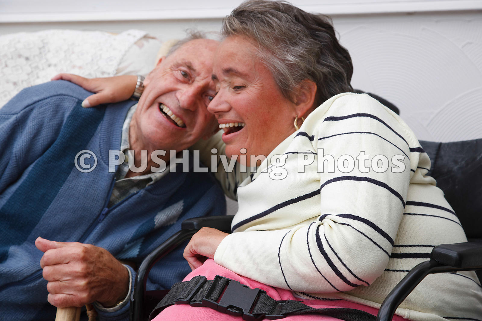 Wheelchair user with Spina Bifida laughing with and embracing her father.