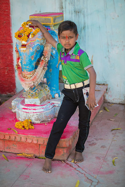A kid poses with their local god in a temple in a village in Bhuj, Gujarat