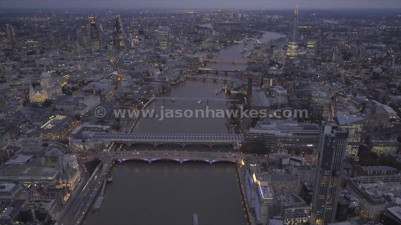 Aerial footage following the River Thames through Central London at dusk
