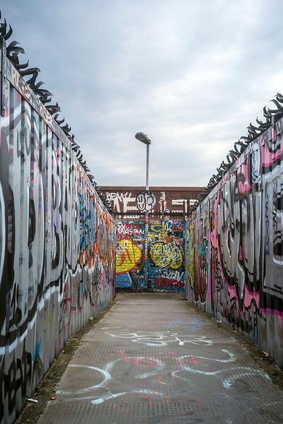 A bridge over a railway line covered in graffiti