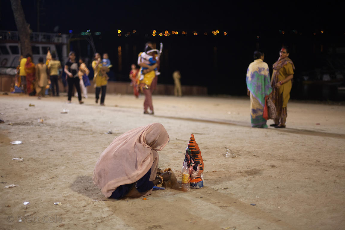 An elderly woman offers prayers to a meager idol during the Lakshmi Puja festival immersion on the Hooghly River at Babughat,...