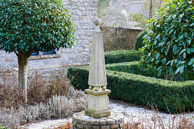 Obelisk in the formal courtyard garden surrounded by box edged beds and standard laurel trees.