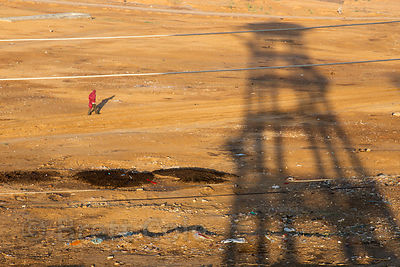 A man walks on desert sands near the shadow of a concrete water tower, Pushkar, Rajasthan, India