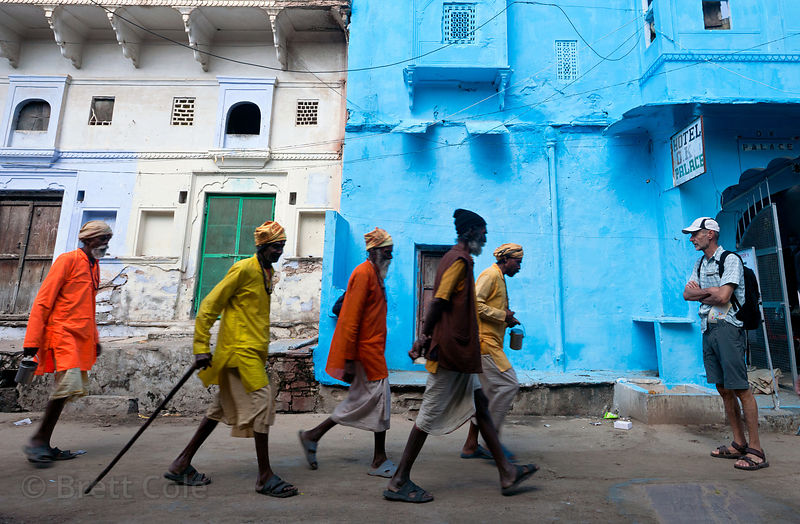 Sadhus and a tourist walk past a vibrant blue building in Pushkar, Rajasthan, India