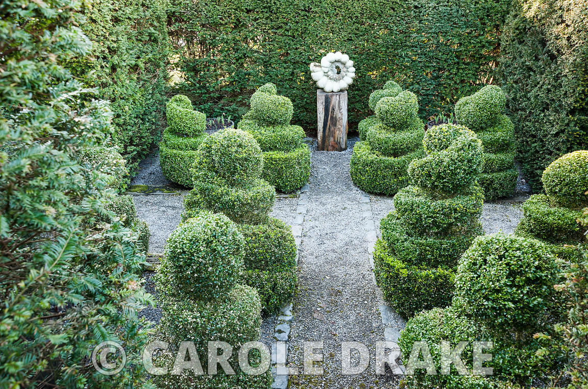 An ammonite sculpture by Darren Yeadon surrounded by box topiary, is set within yew hedges in a formal garden.