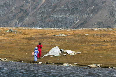 Indian tourists in rented snowsuits take photos at the small lake at Snow Point atop Rohtang Pass (13,054 ft., 3,979 m) in th...