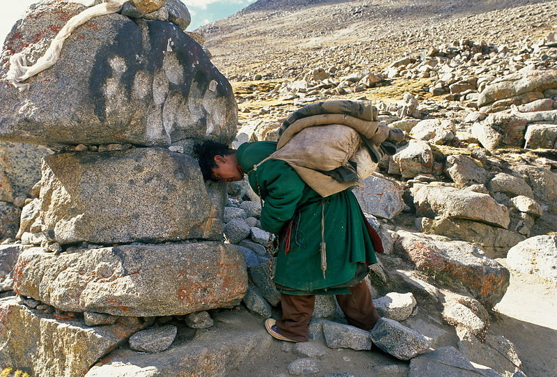 Man praying againts sacred rock