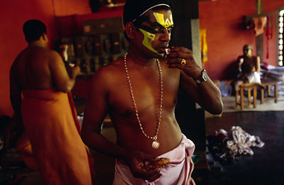 India - Kerala - An actor pauses his make up for a snack before a performance