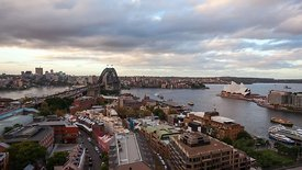 Bird's Eye Billowing Clouds & Sunset Over A Busy Sydney Harbor