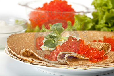 served place setting: pancake with red caviar, sour cream and greens