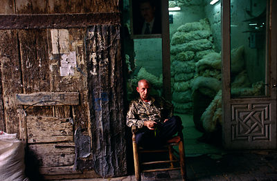 Syria - Aleppo - A man sits outside his shop