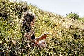 Little girl in the grass picking flowers 2