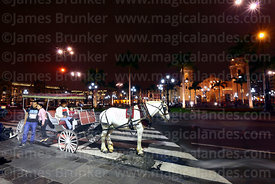 Horse and carriage waiting for passengers, cathedral and Plaza de Armas in background, Lima, Peru