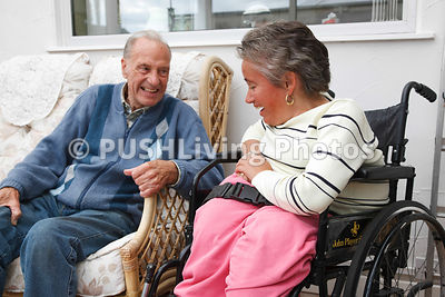 Wheelchair user with Spina Bifida laughing with her father.